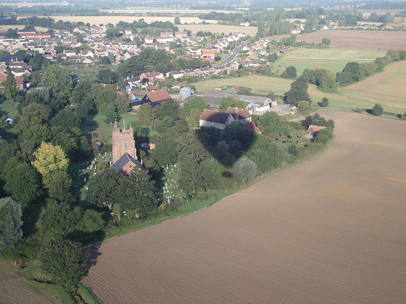 "Black Notley is one of the three ""Notleys"" in Essex near Chelmsford. This is a great aerial picture on a balloon ride floating close to the spire of the local church St Peter and St Paul Black Notley just before landing at the nearby farm in a cut grass field"